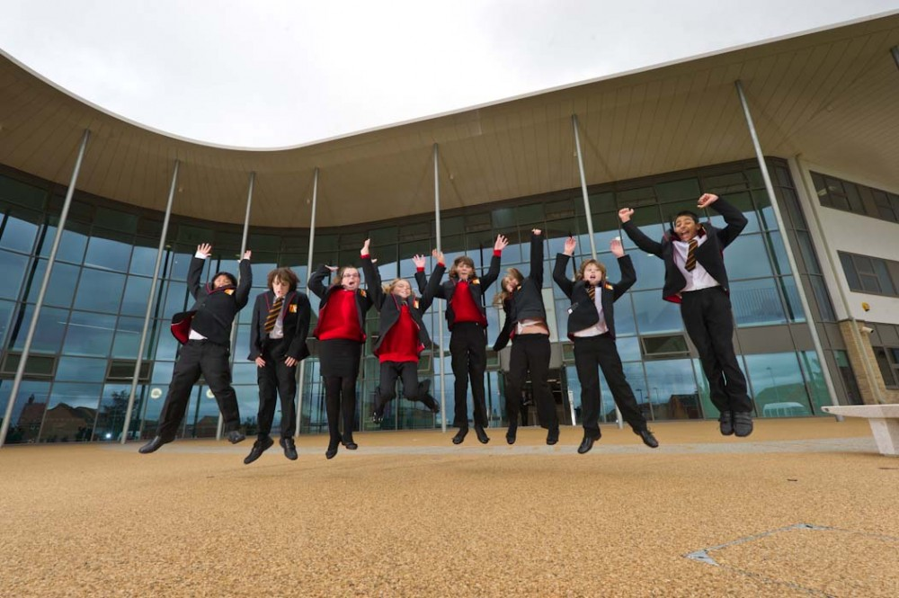 Academy pupils jumping outside school building