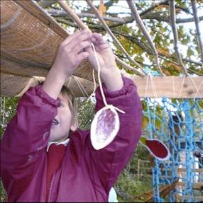 Boy hanging up fruit in temparary sukkot shelter