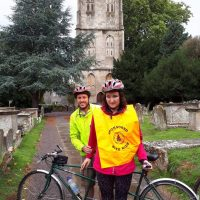 Charlotte and Alex outside a church with their tandem bike