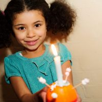 Smiling child holding Christingle