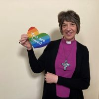 Bishop Rachel holding a heart with the words You are Loved on it