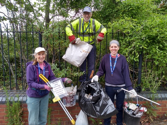 Three people with litter picking equipment and buckets with collected litter