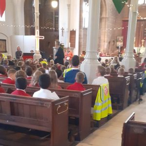 Children sit in the church which is decorated with fairy lights